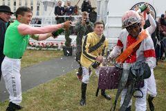 Jockey Eduardo Pedroza bekommt nach seinem ersten Derbysieg mit Laccario eine Sektdusche von den Kollgen. www.galoppfoto.de