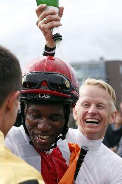 Jockey Eduardo Pedroza bekommt von Jockey Filip Minarik eine Sektdusche nach dem Sieg im IDEE 150. Deutschen Derby mit Laccario. www.galoppfoto.de